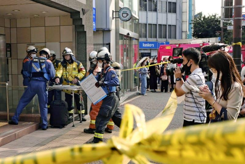 規制線が張られ、消防隊や通行人らで騒然とする福岡市地下鉄空港線の赤坂駅(23日午前、福岡市)=共同