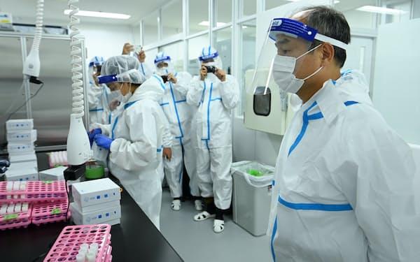 唾液PCR検査施設を視察するソフトバンクグループの孫正義会長兼社長(右)(24日、千葉県市川市)