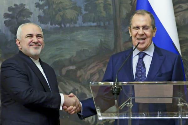 会談後に握手するロシアのラブロフ外相(右)とイランのザリフ外相(24日、モスクワ)=AP