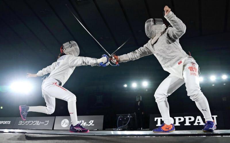 フェンシングの高校生対象のオープン大会・女子サーブル決勝で攻める、優勝した慶応女高・河野真央選手=左(25日、神奈川県箱根町)=共同