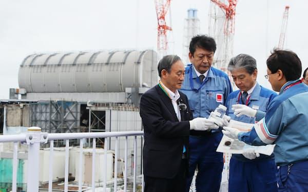 福島第1原子力発電所構内を視察し、多核種除去設備(ALPS)で浄化処理した汚染水を手にする菅首相(26日、福島県大熊町)
