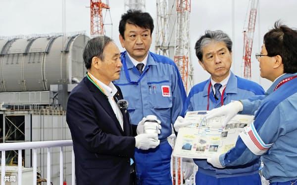東京電力福島第1原発を視察し、浄化処理した汚染水を手にする菅首相=26日午後(代表撮影)
