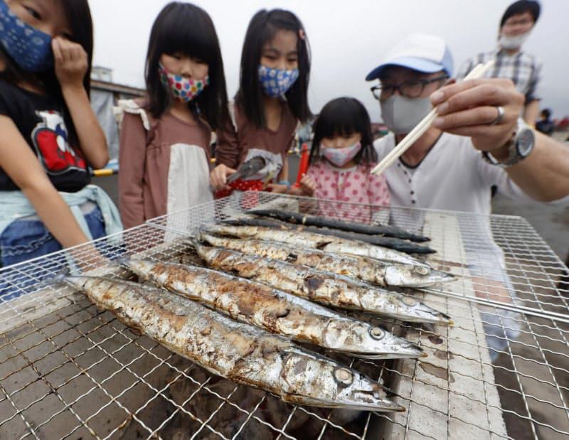 ゆりあげ港朝市の「さんま祭り」で焼かれるサンマ(27日午前、宮城県名取市閖上地区)=共同
