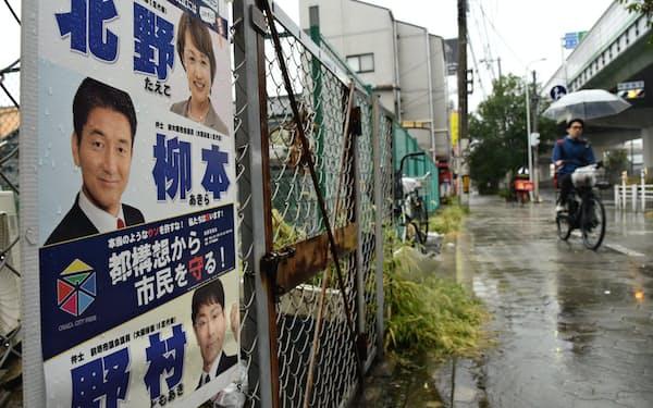 北野氏ら3人が写ったポスターに「自民党」の文字はない(25日、大阪市西成区)