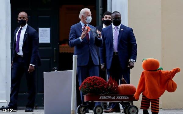 27日、花を手にしながら米デラウエア州の教会を出るバイデン前副大統領=ロイター