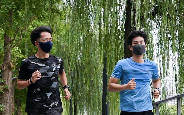 アシックスのスマートシューズを履いて走る記者(右)。体の前傾を意識して路面を蹴るように促された