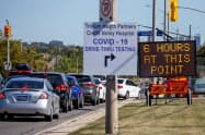 ドライブスルー形式の新型コロナの検査施設には順番待ちの車が並んでいる(18日、カナダのオンタリオ州)=ロイター