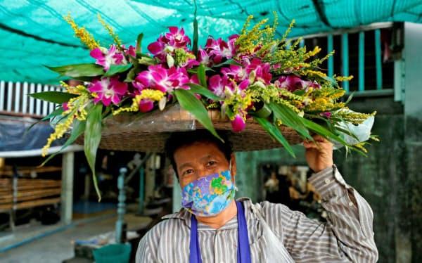 マスク姿で花を売る女性(2日、バンコク)=ロイター
