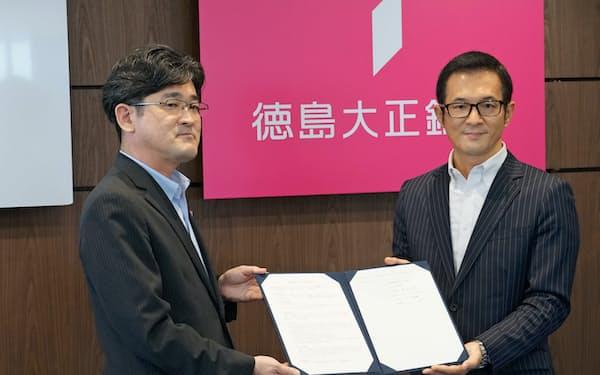 業務提携の調印式に出席した徳島大正銀行の板東頭取(左)とYSKの吉川社長