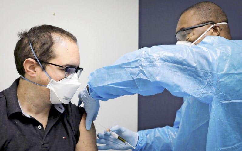 米国内で行われた臨床試験で新型コロナウイルスのワクチン候補を接種されるボランティア(左)=ロイター
