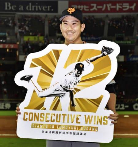 開幕投手から12連勝のプロ野球記録に並び、記念のボードを手にする巨人・菅野(29日、マツダ)=共同