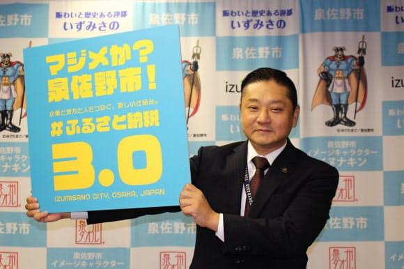 ふるさと納税の新しい仕組みの記者会見後、写真撮影に応じる千代松・泉佐野市長(30日、同市役所)