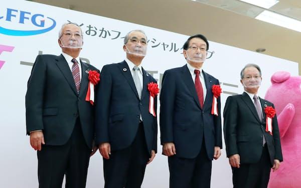 十八親和銀行が発足し、式典に出席した森頭取(左端)と吉沢会長(右端)=1日、長崎市