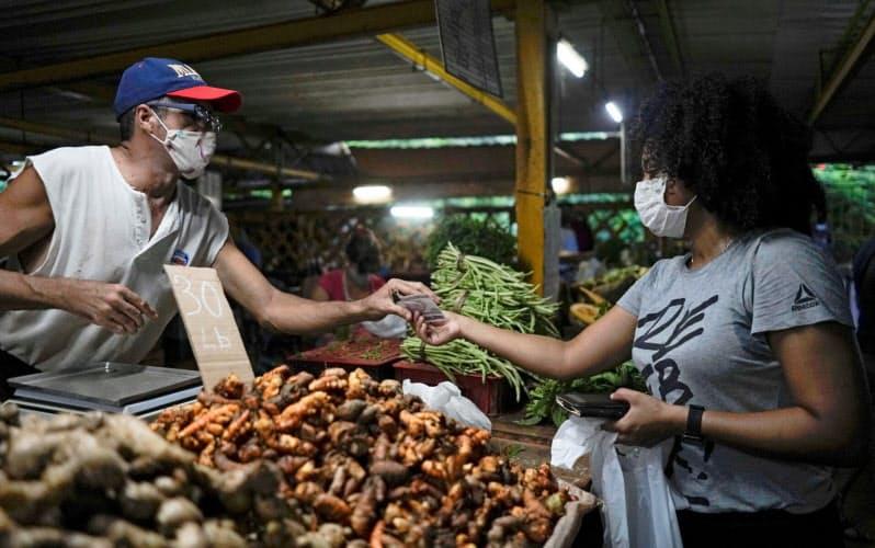新型コロナ対策のためマスクを着けて買い物をするハバナ市民=ロイター