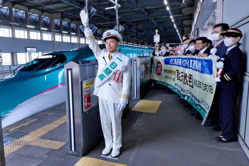 「君は天然色」の発車メロディーが流れるなか、出発の合図をする石川悦哉さん(1日、奥州市)