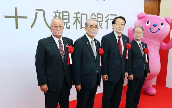 十八親和銀行が発足し、記念写真に納まる森頭取(左端)と吉沢会長(右端)=1日、長崎市