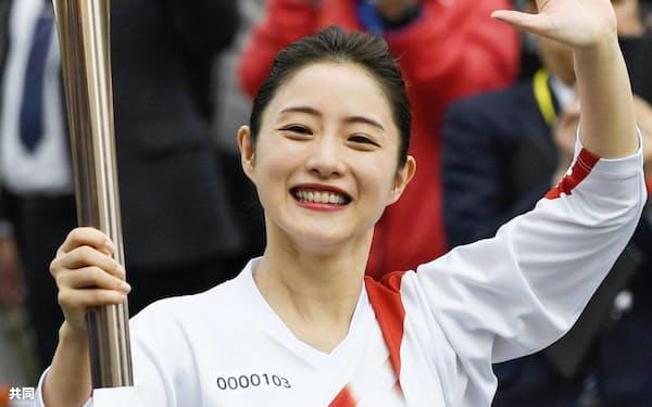 2月、聖火リレーのリハーサルに参加し、笑顔で手を振る俳優の石原さとみさん(東京都羽村市)=共同