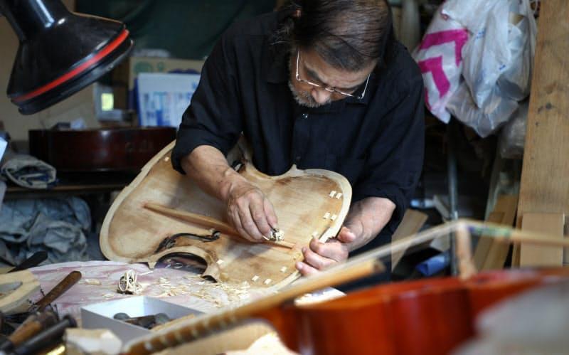 モダンチェロを古楽器として復元するため、音に影響する補強材を削る平山さん=松浦弘昌撮影