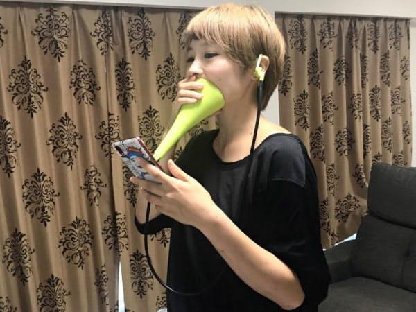 防音グッズを使って、自宅でのカラオケを楽しむ女性会社員(9月、東京都内)