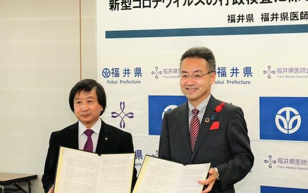 福井県医師会の池端会長(左)と契約締結式に臨む杉本知事(2日、福井県庁)
