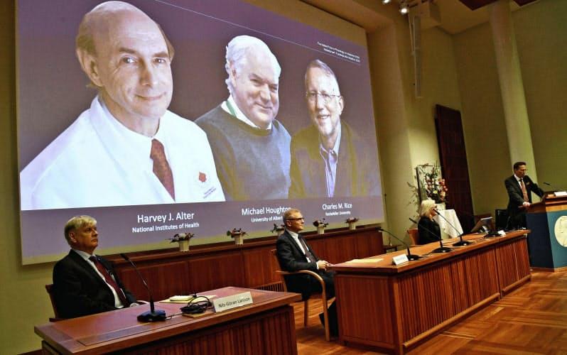 ノーベル生理学・医学賞の受賞が決まった(後ろの画面左から)アルター氏、ホートン氏、ライス氏を発表する記者会見(5日、ストックホルム)=ロイター