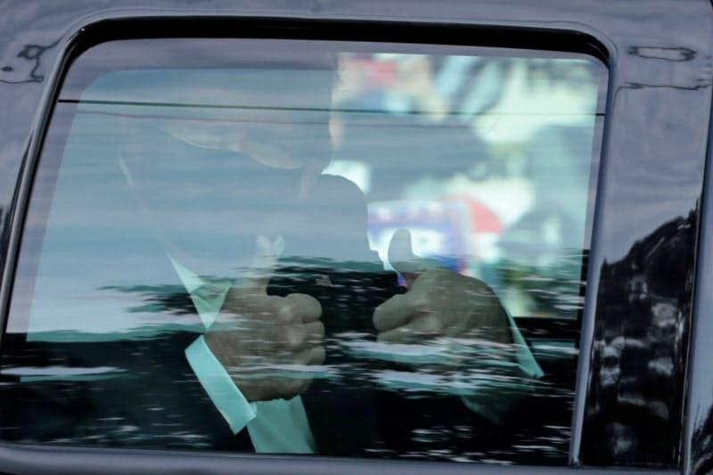 病院の前で車内から親指を立てて支持者に応えるトランプ大統領(4日、米メリーランド州)=ロイター