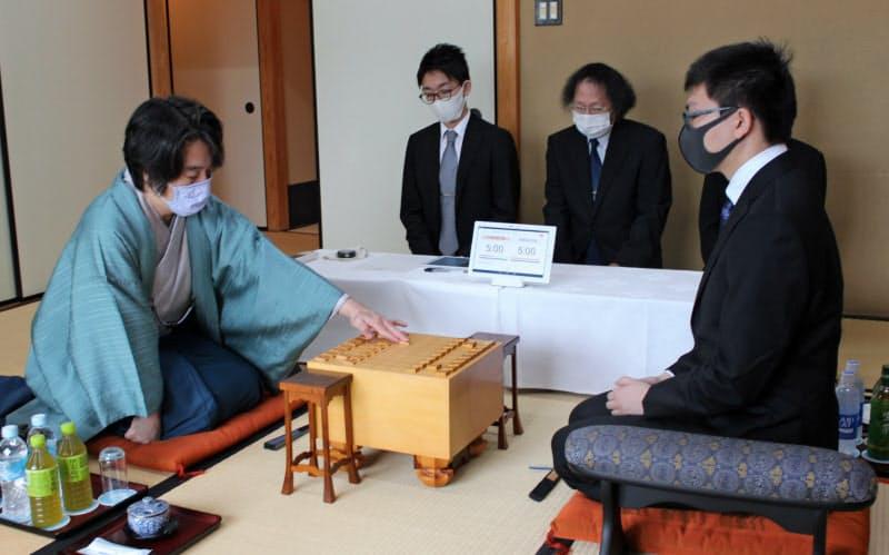 王座戦第4局で初手を指す久保九段(左、6日午前、神戸市)