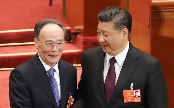 2018年3月、任期制限のない国家副主席に選ばれた王岐山氏(左)と握手する習近平国家主席(北京の人民大会堂)=三村幸作撮影