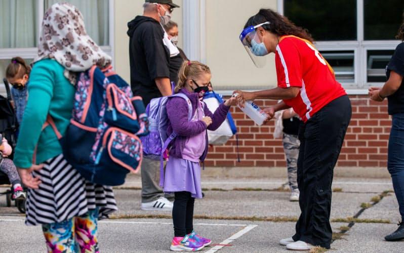 カナダ・オンタリオ州の公立学校では通学かオンライン授業かが選べる(9月、手を消毒してもらう子ども)=ロイター
