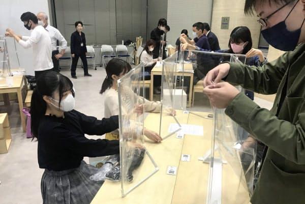 対面授業を前にパーティションを組み立てる大阪市大の学生。机にはQRコードも