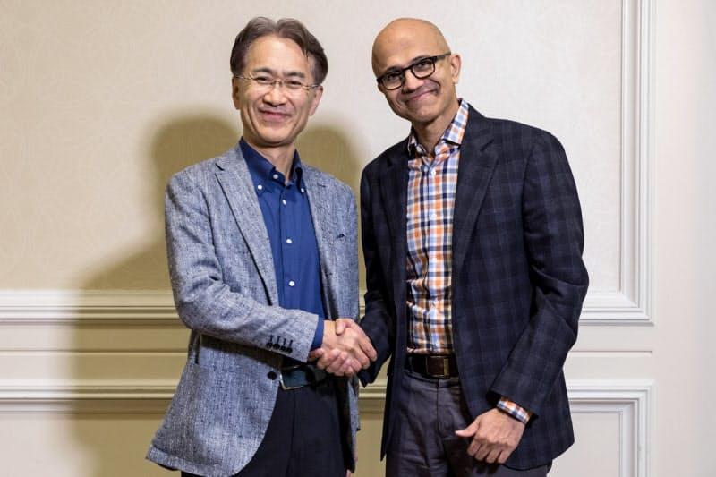 クラウドやAIで提携する一方、ゲーム機では激しく激突する。(握手するソニーの吉田会長兼社長(左)とマイクロソフトのサティア・ナデラCEO)
