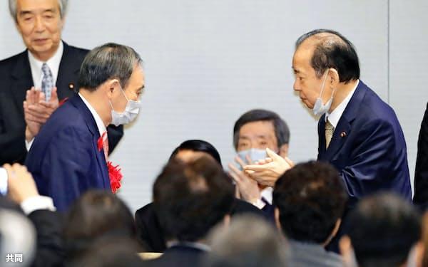 自民党の二階幹事長(右)が率いる二階派の政治資金パーティーに出席した菅首相(左)=7日午後、東京都千代田区