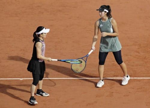 女子ダブルス準々決勝でラケットでタッチを交わす青山(左)、柴原組(7日、パリ)=AP