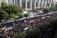 7日、アテネの裁判所前に集まって反ファシズムなどを訴える市民ら=ロイター