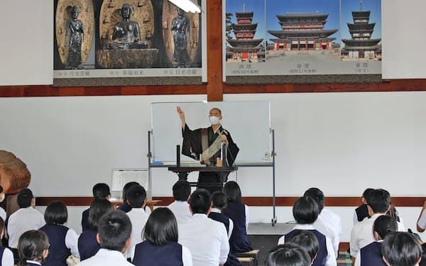 マスクを着けてアクリル板越しに法話をする薬師寺の僧侶(奈良市)