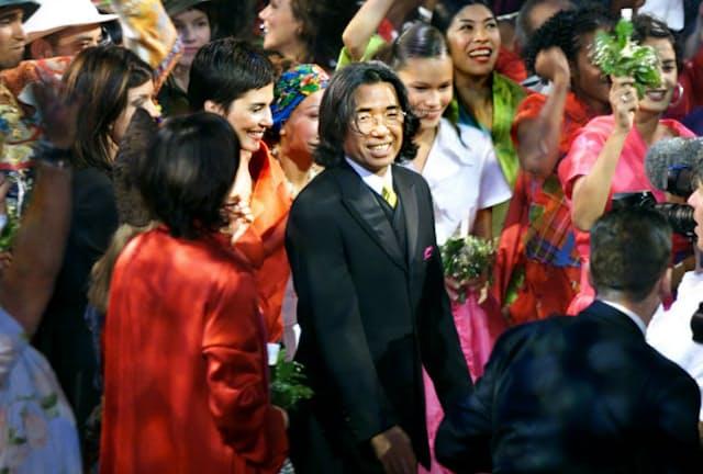 1999年10月、パリで開いたファッションショーで、モデルらに祝福される高田賢三さん=ロイター