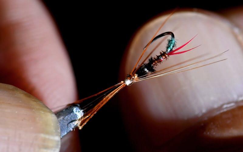 虫の脚をまねた「ミノ毛」は指の爪を針先に当てながら均一に並んでいるか確認する=笹津敏暉撮影