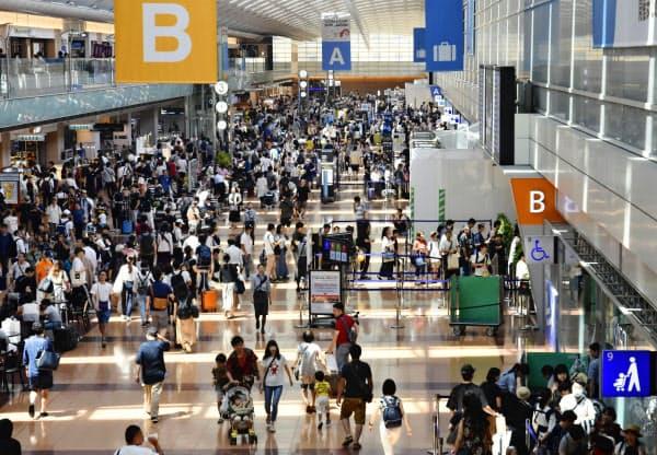 旅行客でにぎわう羽田空港国内線ターミナル(8月)=共同