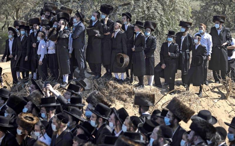 5日、イスラエル南部アシュドッドで宗教指導者の葬儀に集まったユダヤ教超正統派の人々=AP