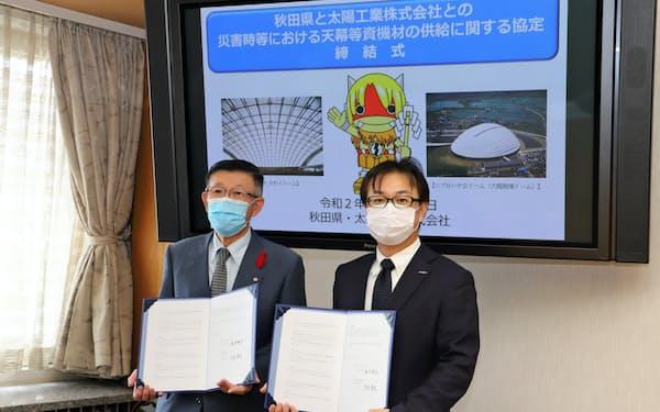 協定を結んだ太陽工業の荒木秀文社長(右)と、秋田県の佐竹敬久知事(13日、秋田県庁)