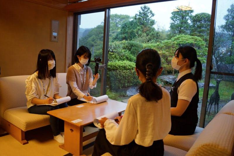 長生閣で広報担当の松鹿さん(右)を取材する女子学生