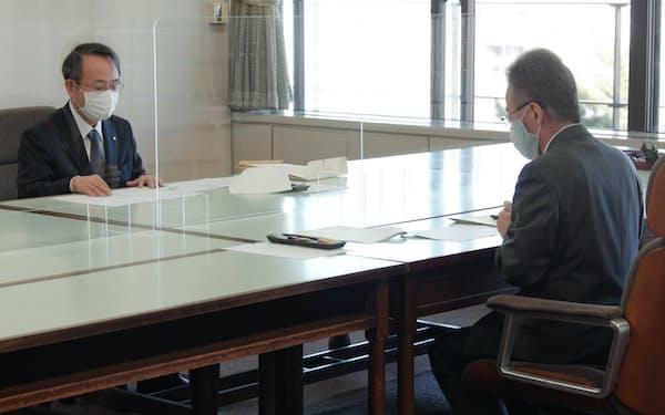 関西電力の森本社長(左)は福井県の杉本知事に業務改善計画の実施状況などを説明した(14日、福井県庁)