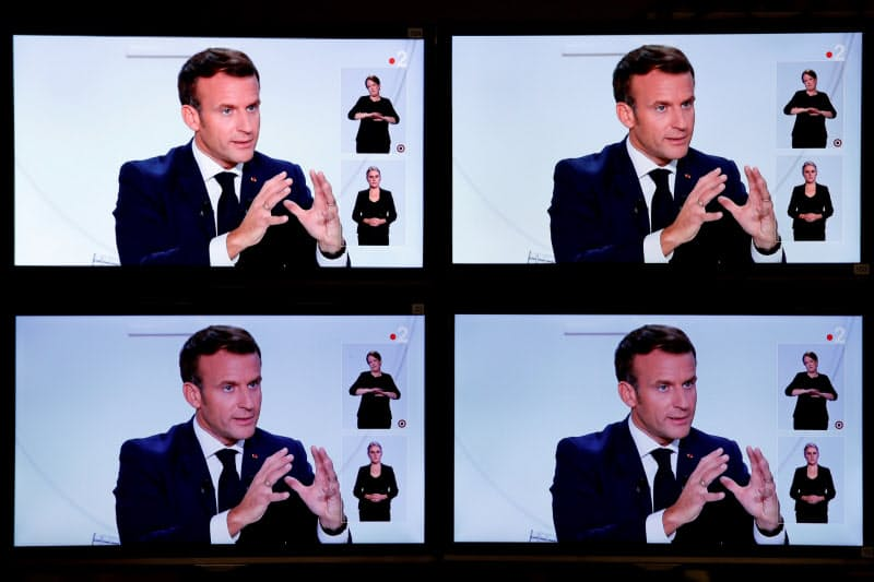 14日、仏テレビの取材を受けるマクロン仏大統領=ロイター