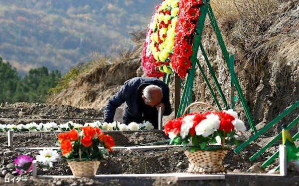 紛争の犠牲者を悼む人(14日、ナゴルノカラバフ)=ロイター