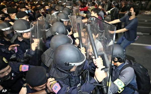 15日、デモ隊と衝突する警官隊(バンコク)=AP