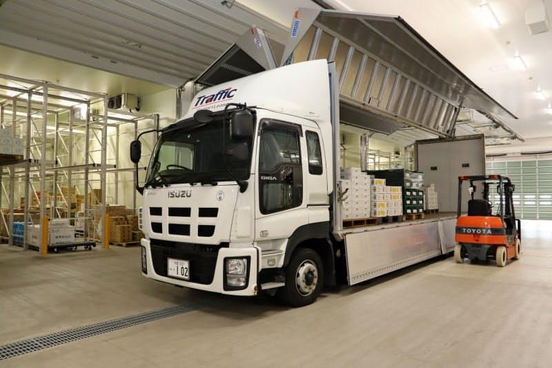 冷蔵庫の前で大型トラックから荷下ろしできる(15日、秋田市の「松紀 秋田南青果センター」)