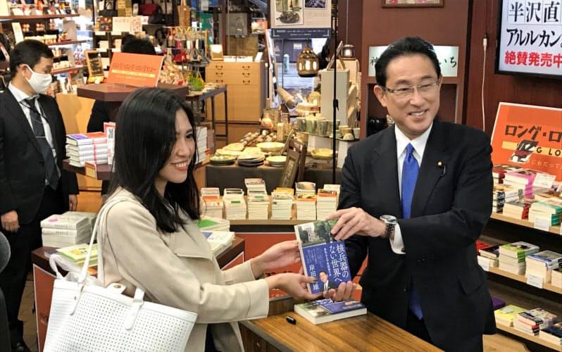 都内の書店を訪れ、自著出版をアピールする自民党の岸田氏(右)(15日、東京・千代田)