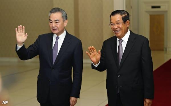 カンボジアのフン・セン首相と面会する王毅外相(12日、プノンペン)=AP