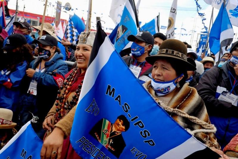 モラレス前大統領の写真が印刷された旗を持つ、左派陣営の支援者(14日、ラパス近郊)=ロイター
