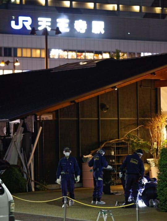 男性が刺された現場付近を調べる大阪府警の警察官ら。奥はJR天王寺駅(18日午後6時24分、大阪市の天王寺公園)=共同